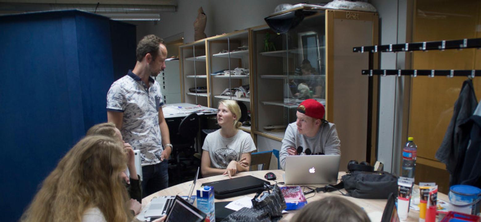 Studenten overleggen met een docent