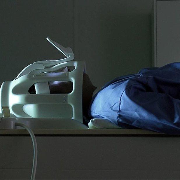 Patient met masker in MRI-scanner