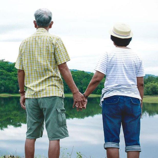 Man en vrouw kijken hand in hand naar landschap met water