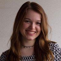 Een jonge vrouw met bruinrood haar, een ketting en een shirt met een zwart-wit patroon kijkt lachend in de camera.