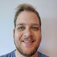Een jonge man met blond haar, een snor en baard en een lichtblauw t-shirt kijkt glimlachend in de camera.