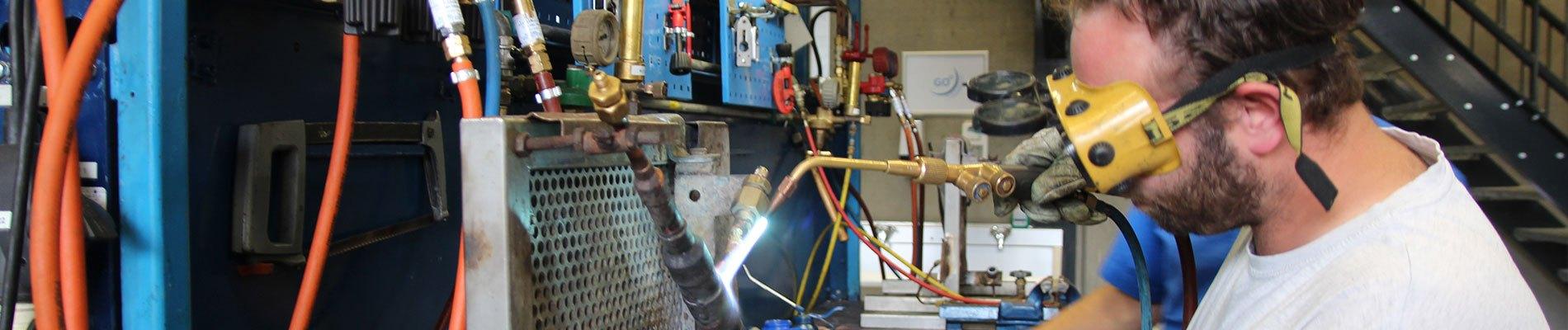 Man aan het solderen bij koelinstallatie
