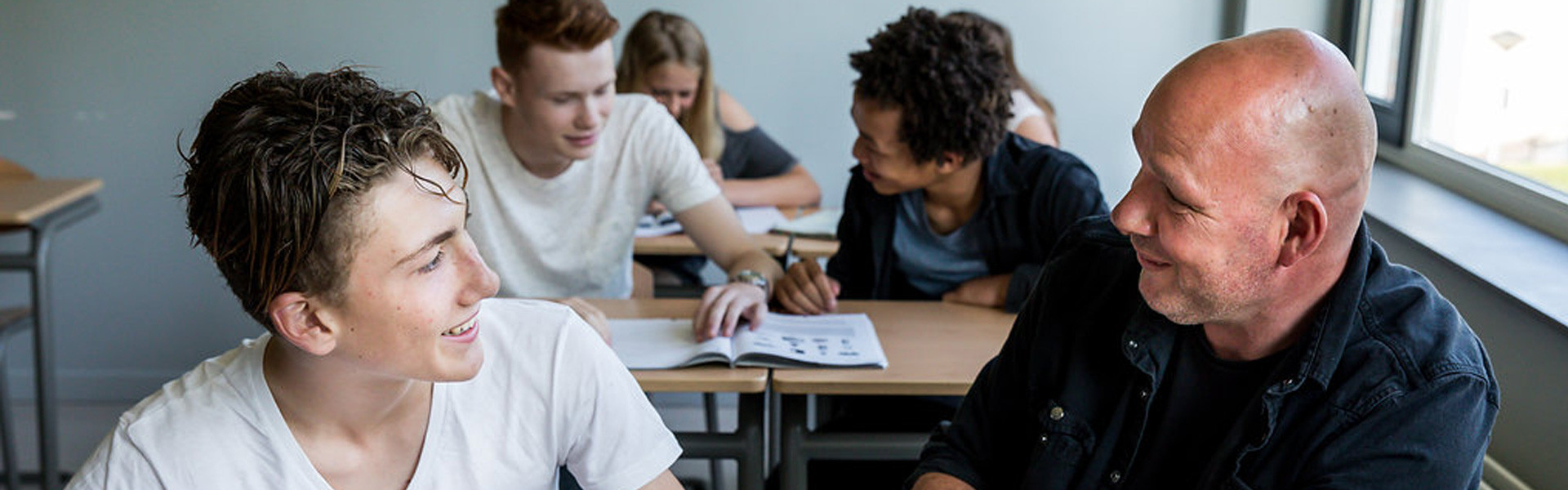 Enthousiaste docent is in gesprek met leerling
