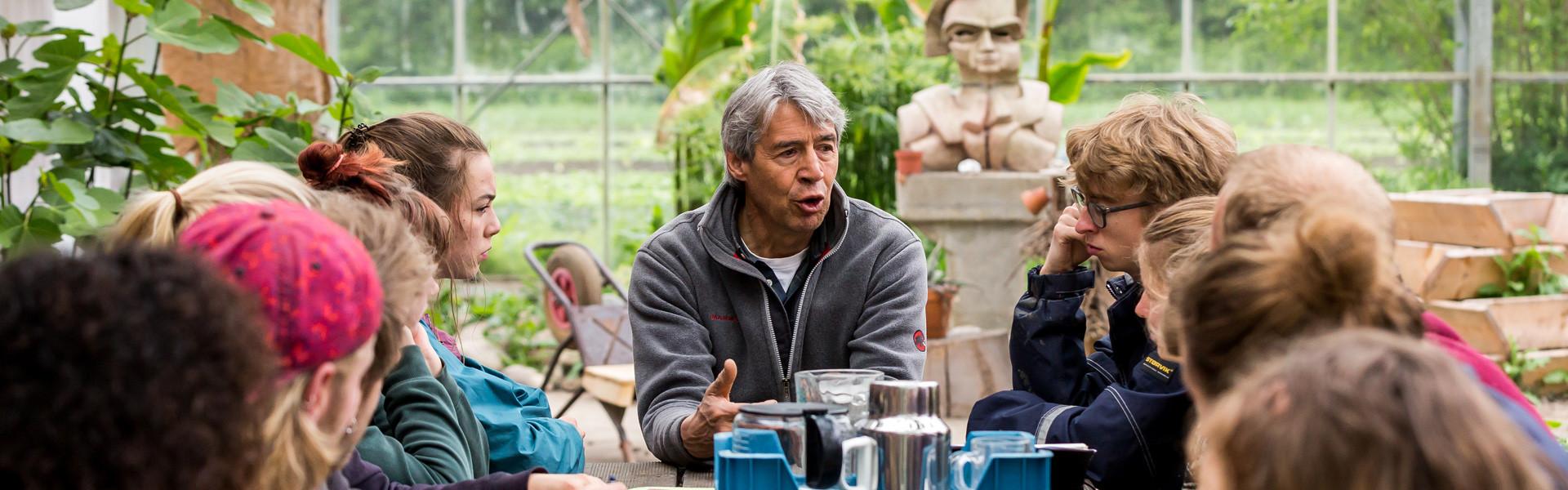 Docent geeft les aan een groep studenten in een kas.