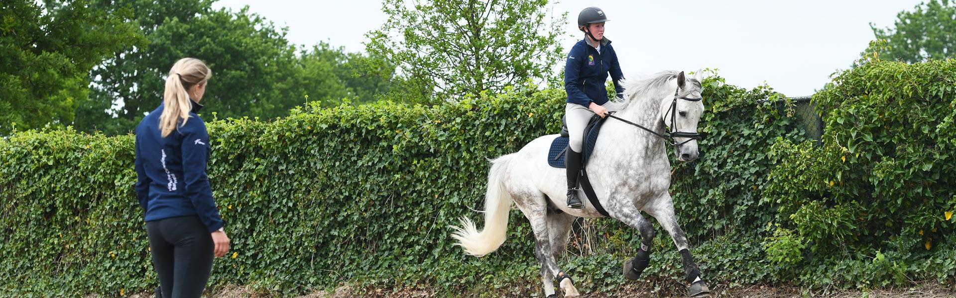 Instructeur met leerling op een paard