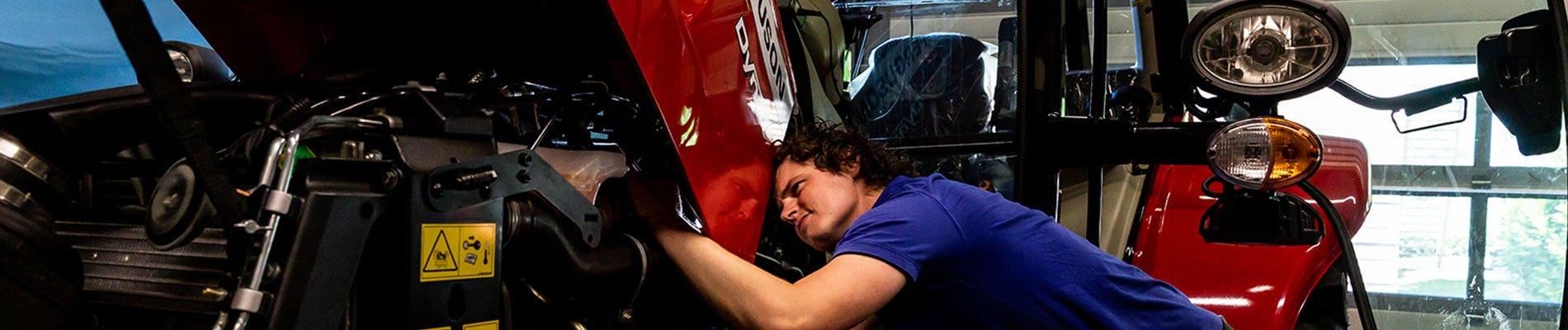 Leerling repareert tractor